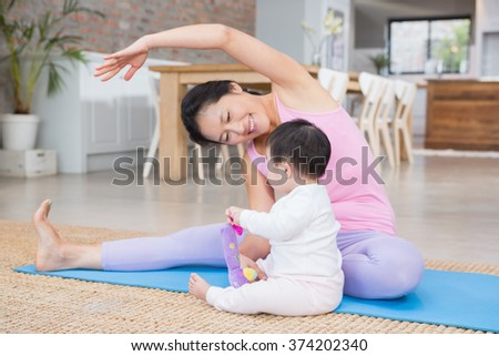 Happy mother doing yoga on mat while looking at baby daughter at home - stock photo
