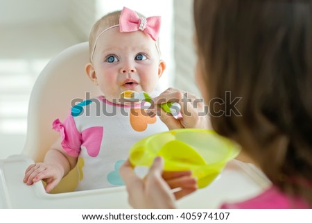 Happy mother eating with her baby at home