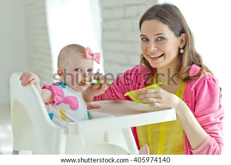 Happy mother eating with her baby at home  - stock photo