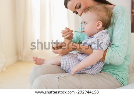 Happy mother eating with her baby boy at home in bedroom - stock photo