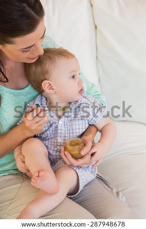 Happy mother eating with her baby boy at home in living room