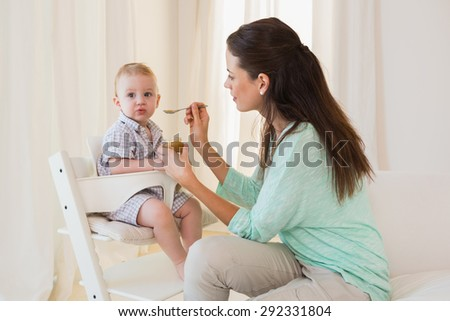 Happy mother eating with her baby boy at home in living room - stock photo
