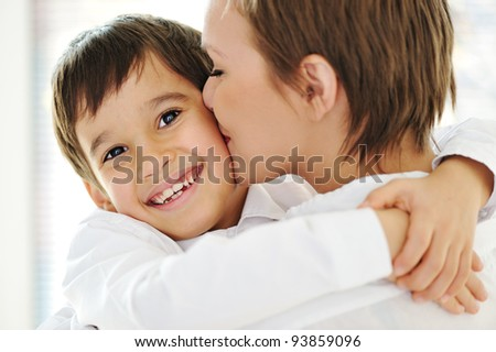 Happy mother embracing and kissing her son - stock photo
