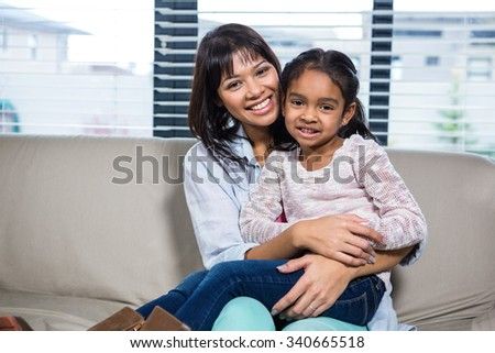Happy mother embracing her daughter in living room - stock photo