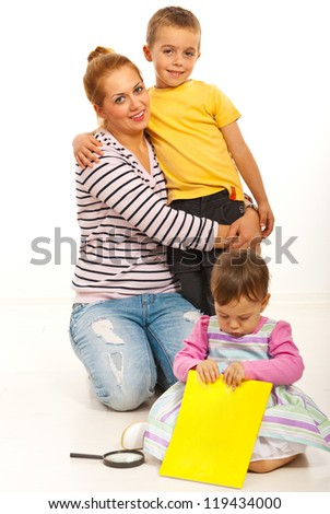 Happy mother embracing her son while her daughter playing with a book - stock photo
