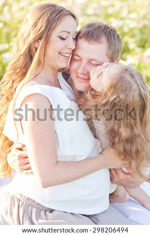 Happy mother, father and daughter in the camomile field have a picnic - stock photo