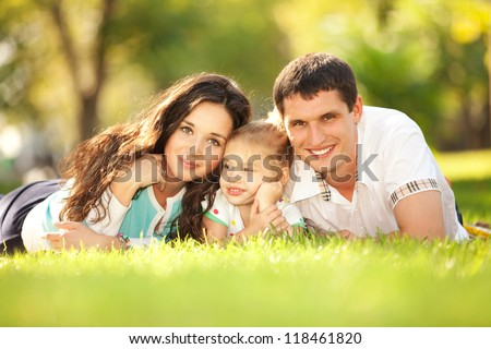 Happy mother, father and daughter in the park. Beauty nature scene with family outdoor lifestyle. Happy family resting together on the green grass. Happiness and harmony in family life.