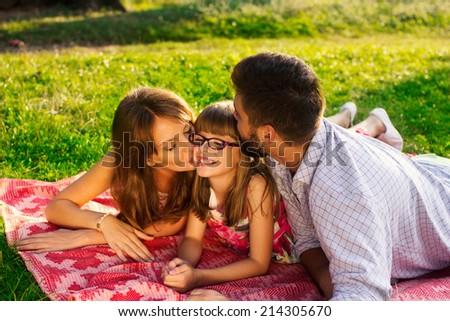 Happy mother, father kissing their daughter in the park - stock photo