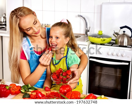 Happy mother feed child at kitchen. - stock photo