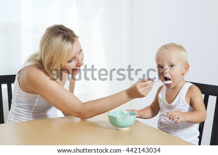Happy mother feeds her child from spoon. Family have breakfast at home. - stock photo