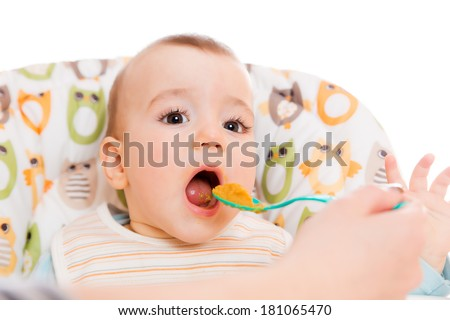 Happy mother feeds hungry baby from a spoon - stock photo