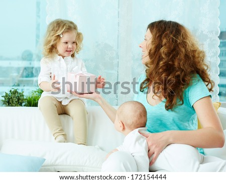 Happy mother giving a present in giftbox to her little daughter - stock photo