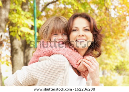 Happy mother giving piggyback ride. Shallow focus. - stock photo