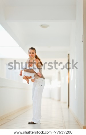Happy mother having fun time with baby outdoor - stock photo