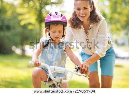 Happy mother helping baby girl riding on bicycle - stock photo