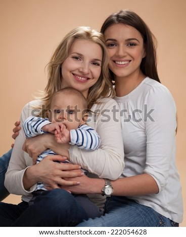 Happy mother, her baby boy and sister posing for family portrait. - stock photo