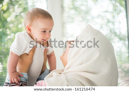 Happy mother holding a beautiful little baby - stock photo