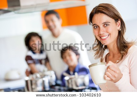 Happy mother holding a cup of coffee in the kitchen - stock photo