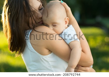 Happy mother holding a young sleeping son in the park - stock photo