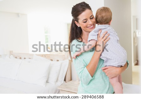 Happy mother holding baby boy at home - stock photo