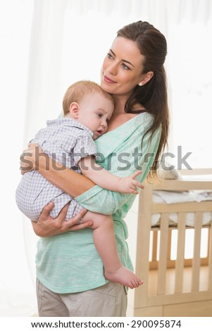Happy mother holding baby boy at home in bedroom - stock photo