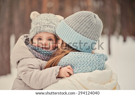 happy mother holding baby girl on the walk in winter snowy forest - stock photo