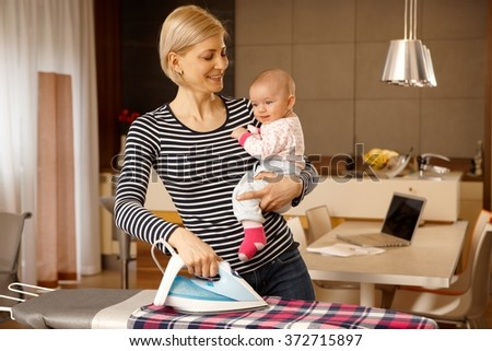 Happy mother holding baby in arm, ironing.
