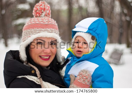 Happy mother holding baby in winter park - stock photo