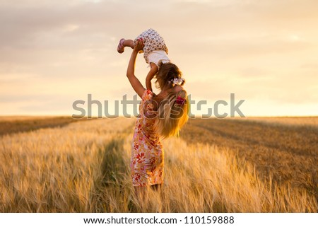 happy mother holding baby smiling on a wheat field in sunlight. outdoor shot - stock photo