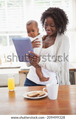 Happy mother holding baby son while using tablet pc at home in the kitchen - stock photo