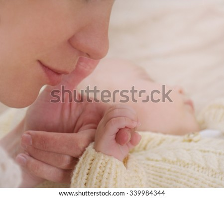 happy mother holding hand her newborn baby; maternity concept; soft image of beautiful family - stock photo