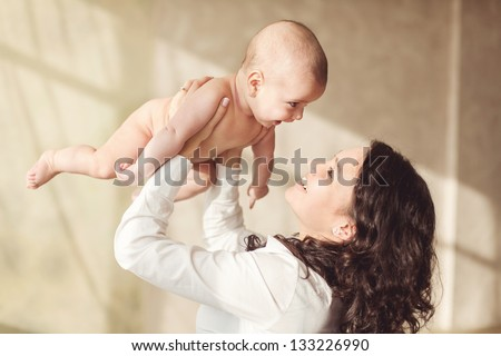 happy mother holding her baby and playing with him indoors - stock photo