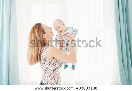 Happy mother holding her baby with love - stock photo