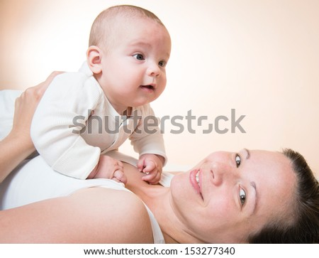 happy mother holding her cute baby, orange background - stock photo