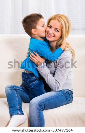 Happy mother holding her son while he is kissing her.Little boy kissing his mother