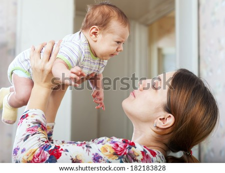 Happy mother holding  young baby  in home interior - stock photo