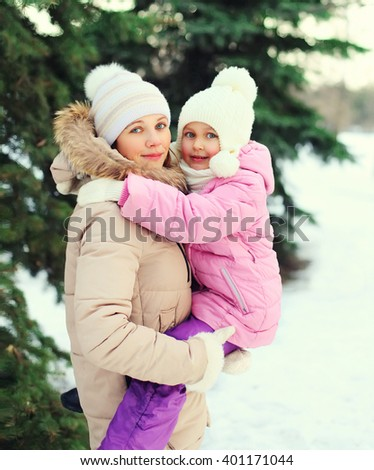 Happy mother hugging child near christmas tree in winter day