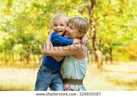 Happy mother hugging child son in park