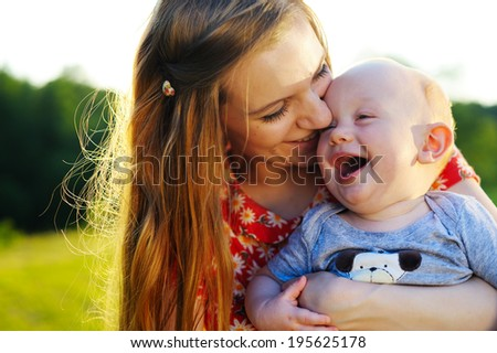 Happy mother hugging her baby - stock photo