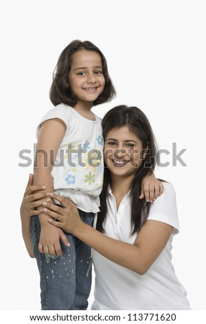 Happy mother hugging her daughter and smiling - stock photo