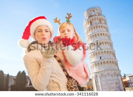 Happy mother in Christmas hat and daughter wearing funny reindeer antlers giving air kiss in front of Leaning Tour of Pisa, Italy. They spending exciting Christmas time traveling. - stock photo