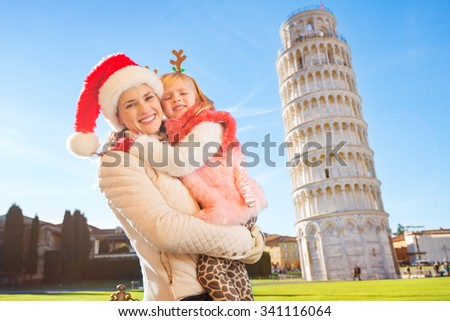 Happy mother in Christmas hat and daughter wearing funny reindeer antlers hugging in front of Leaning Tour of Pisa, Italy. They spending exciting Christmas time traveling. - stock photo