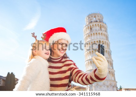 Happy mother in Christmas hat and daughter wearing funny reindeer antlers taking selfies in front of Leaning Tour of Pisa, Italy. They spending exciting Christmas time traveling. - stock photo