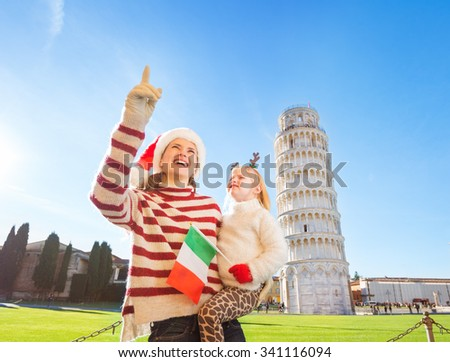 Happy mother in Christmas hat pointing on to daughter wearing funny reindeer antlers and holding Italian flag in front of Leaning Tour of Pisa, Italy. They spending exciting Christmas time traveling. - stock photo