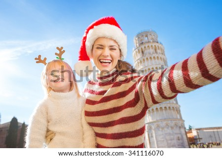 Happy mother in Christmas hat taking selfie with daughter wearing funny reindeer antlers while standing in front of Leaning Tour of Pisa, Italy. They spending exciting Christmas time traveling - stock photo