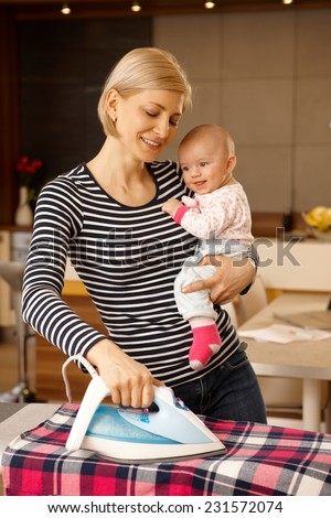 Happy mother ironing at home, holding baby in arm, smiling. - stock photo
