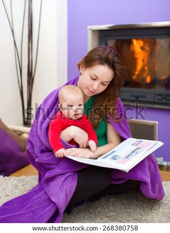 Happy mother is reading book with cute daughter