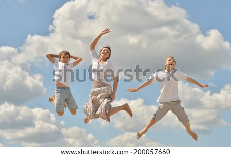 Happy mother jumping with her sons on sky background