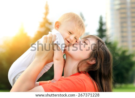 Happy Mother kiss a Little Baby outdoor - stock photo