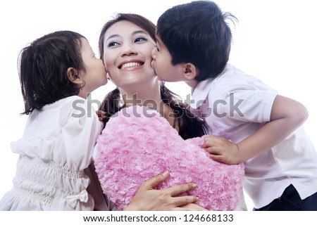 Happy mother kissed by her daughter and son isolated over white background